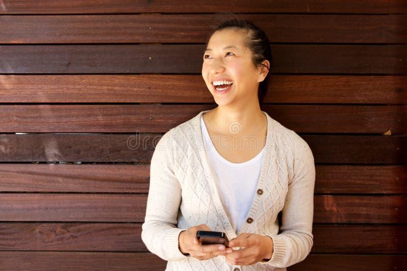 Привлекательная женщина смеясь над с мобильным телефоном против деревянной стены стоковая фотография