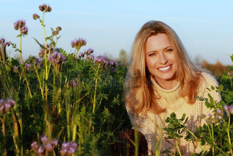 Привлекательная женщина среднего возраста сидя в поле цветка сирени стоковые изображения rf