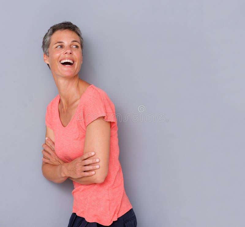 Привлекательная женщина среднего возраста смеясь над против серой стены стоковое фото rf