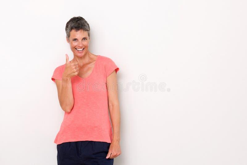 Привлекательная женщина среднего возраста усмехаясь с большими пальцами руки вверх стоковое изображение rf