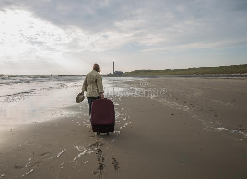Привлекательная женщина с большим чемоданом идет вдоль пустого пляжа o стоковые изображения rf