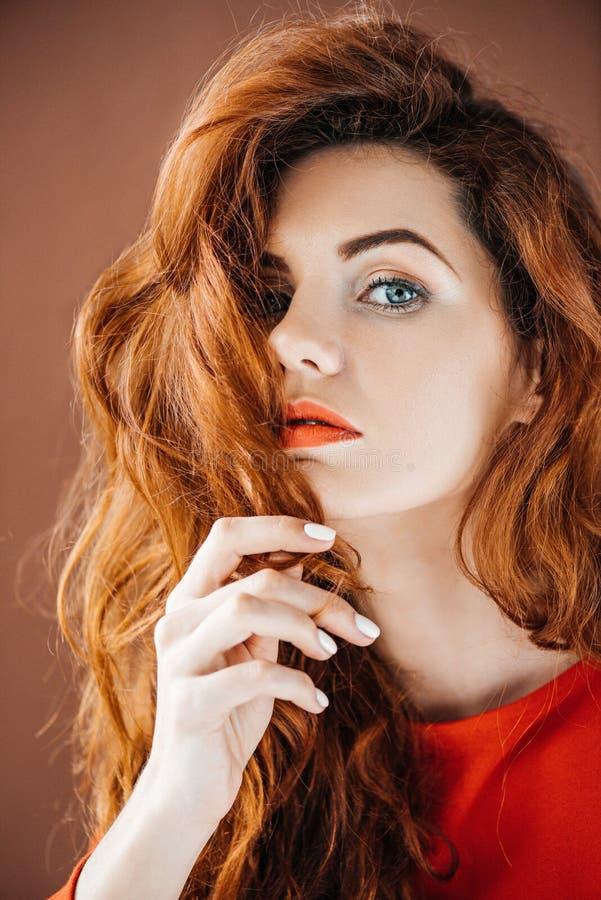 Привлекательная женщина redhead касаясь волосам стоковые изображения