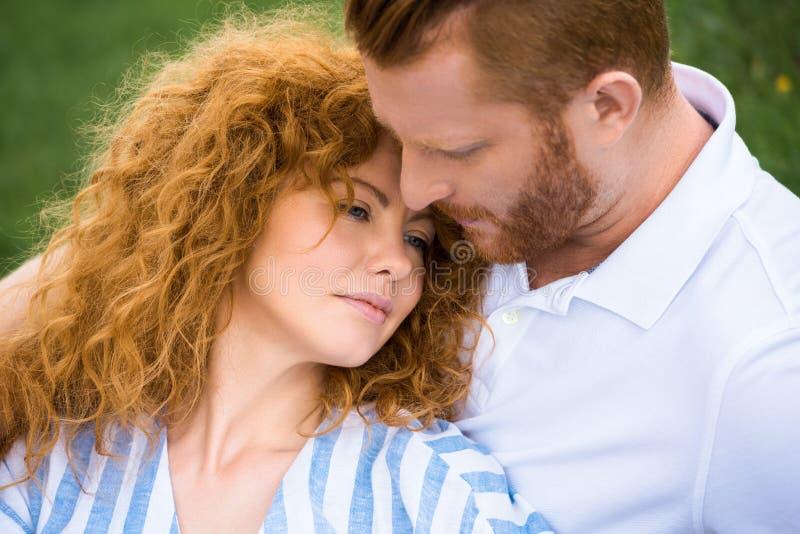 привлекательная женщина redhead кладя на парня стоковые фото