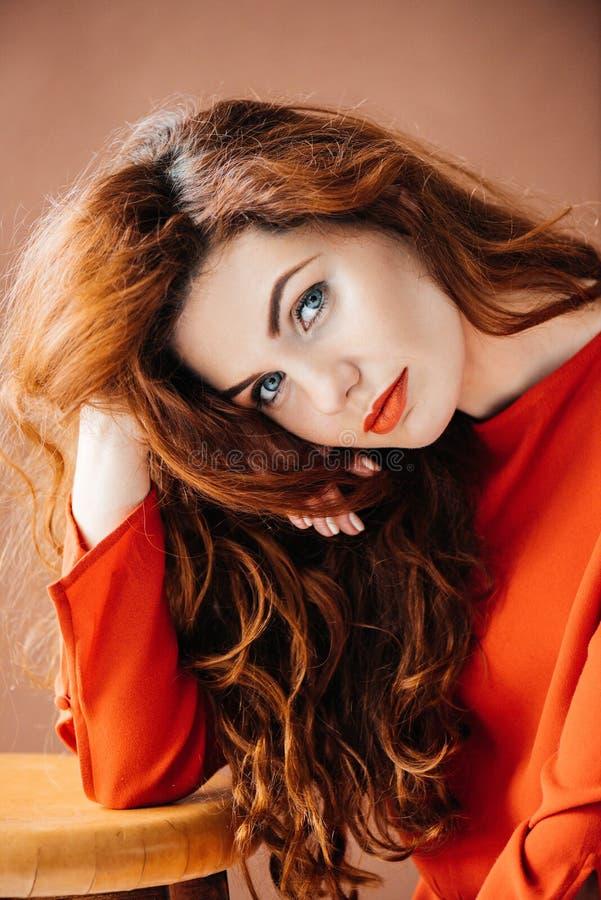 Привлекательная женщина redhead полагаясь на табуретке стоковые изображения rf