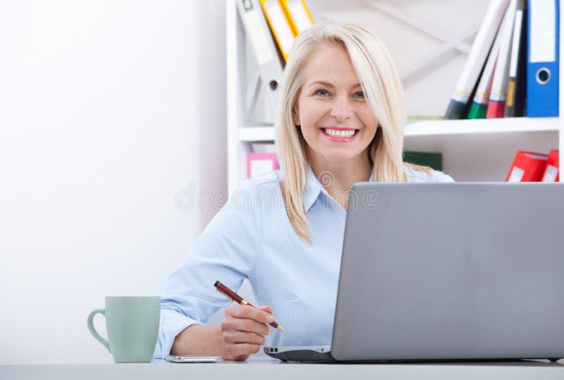 Привлекательная зрелая коммерсантка работая на компьтер-книжке в ее рабочем месте стоковая фотография