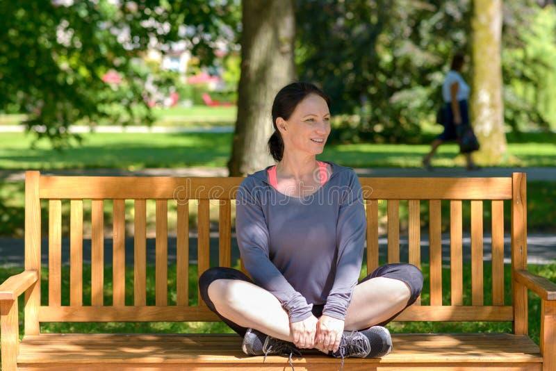 Привлекательная изгибчивая женщина сидя на скамейке в парке стоковое фото