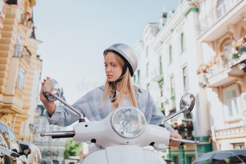 Привлекательная и серьезная белокурая девушка сидящ и смотрящ в зеркале Девушка снаружи на дороге Солнечное снаружи стоковые фотографии rf