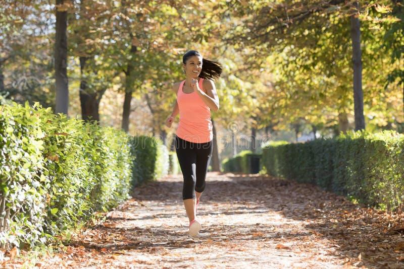 Привлекательная и счастливая женщина бегуна в ходе и тренировке sportswear осени на jogging outdoors разминка в парке города стоковое фото