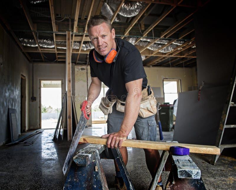 Привлекательная и уверенно древесина вырезывания человека плотника или построителя конструктора работая с руководством увидела на стоковые фотографии rf