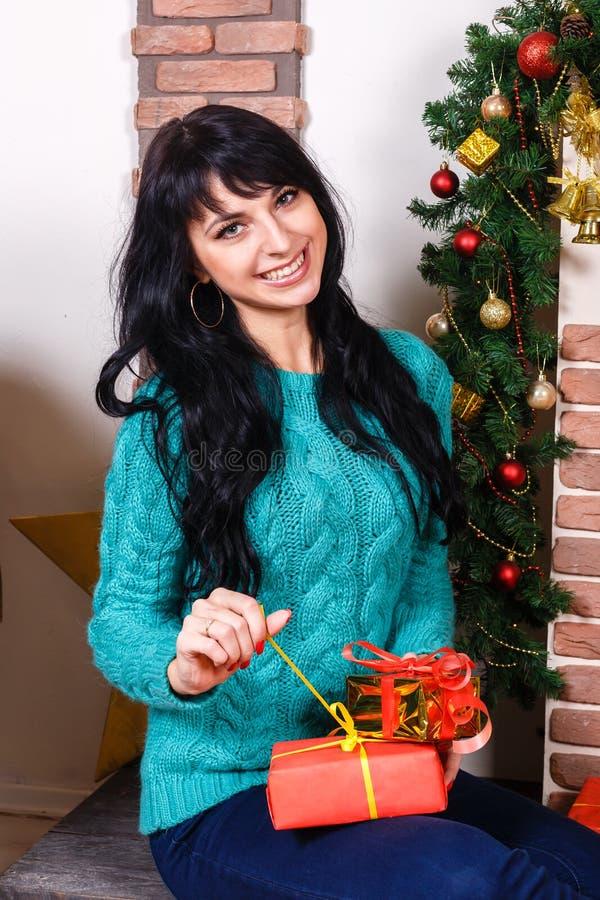 Привлекательная кавказская девушка сидя в комнате с рождеством взаимо- стоковая фотография rf