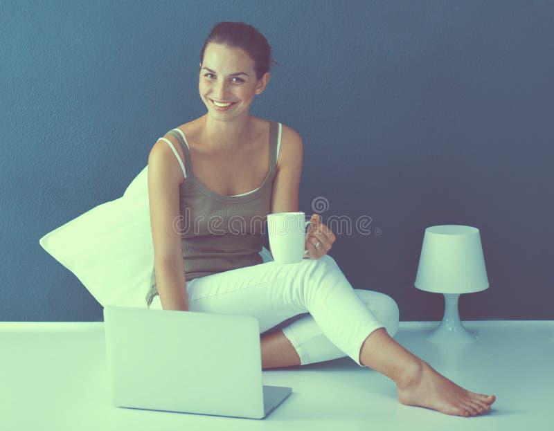 Привлекательная кавказская девушка сидя на поле с ноутбуком стоковые изображения