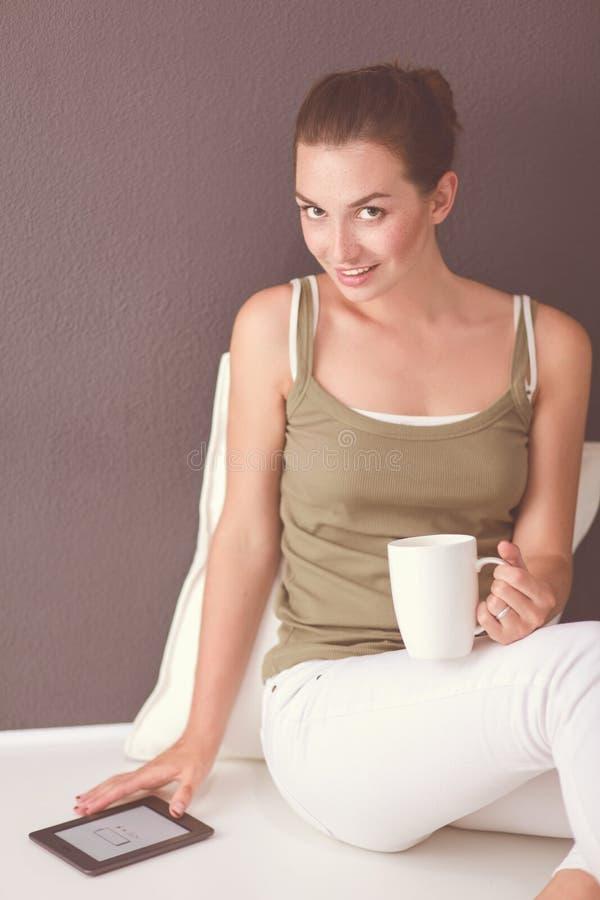 Привлекательная кавказская девушка сидя на поле с чашкой и таблеткой около стены стоковое фото