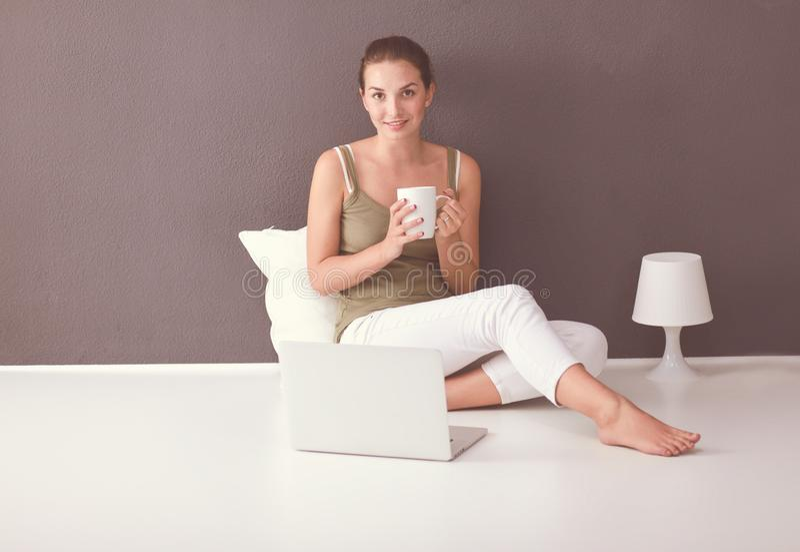 Привлекательная кавказская девушка сидя на поле с чашкой и таблеткой около стены стоковые изображения