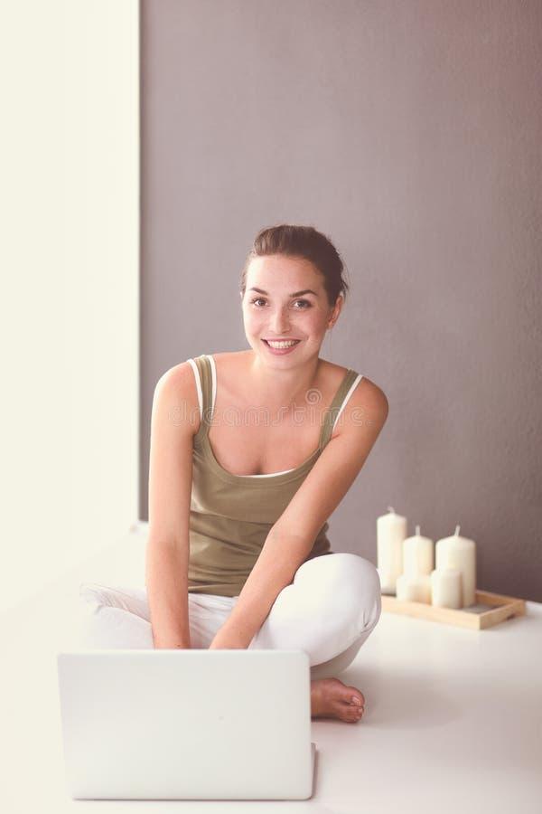 Привлекательная кавказская девушка сидя на поле с чашкой и таблеткой около стены стоковая фотография rf