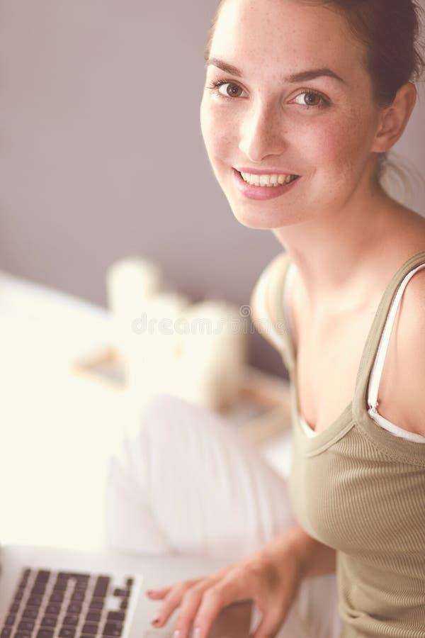 Привлекательная кавказская девушка сидя на поле с чашкой и таблеткой около стены стоковое изображение