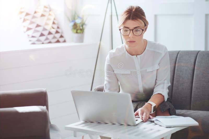 Привлекательная коммерсантка напряженной работы фокусируя на ее работе стоковое изображение