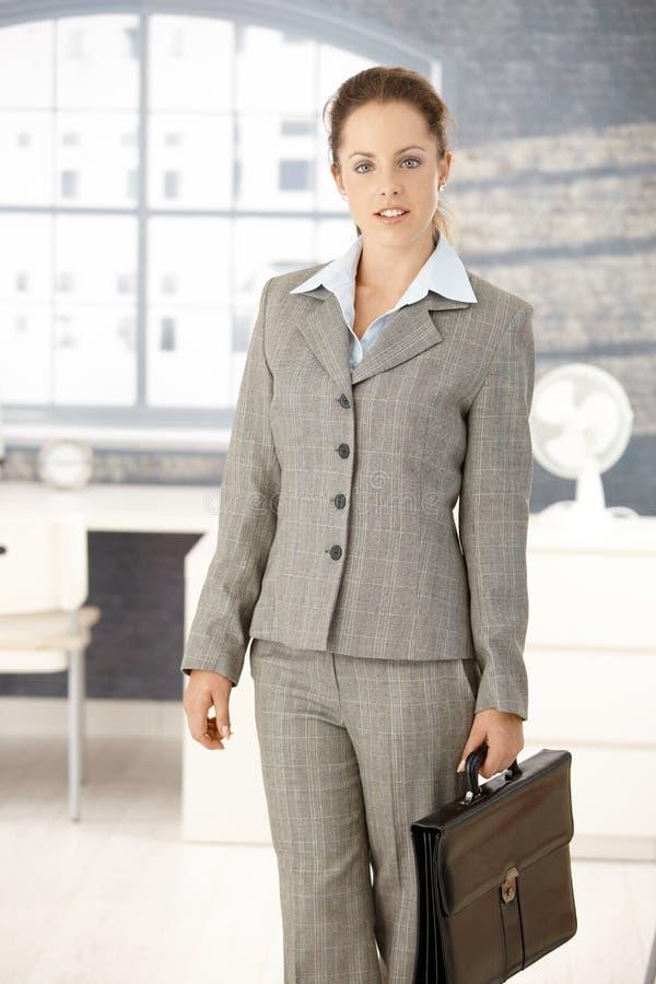 Привлекательная коммерсантка приезжая к яркому офису стоковое фото