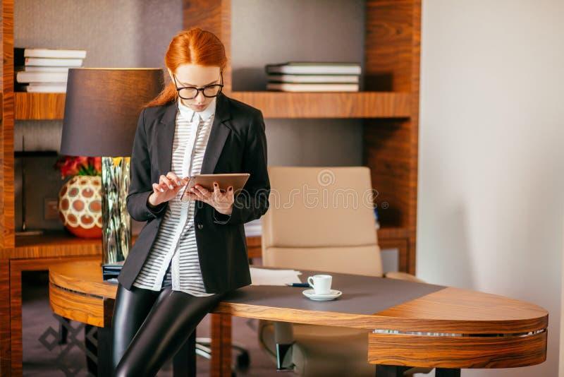 Привлекательная коммерсантка работая на цифровой таблетке в офисе стоковые изображения rf