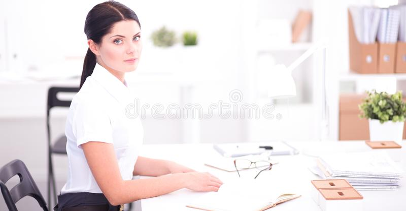 Привлекательная коммерсантка сидя в изолированном офисе, стоковое фото rf