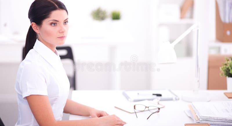 Привлекательная коммерсантка сидя в изолированном офисе, стоковое фото