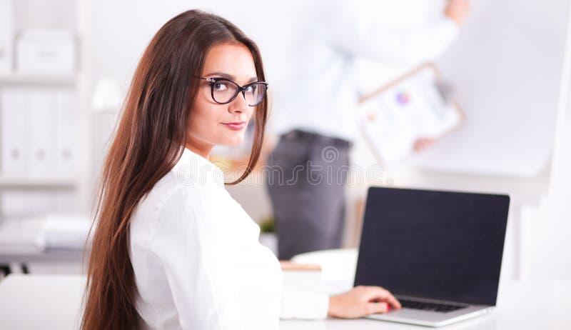Привлекательная коммерсантка сидя в офисе, на столе Привлекательная коммерсантка стоковое фото rf