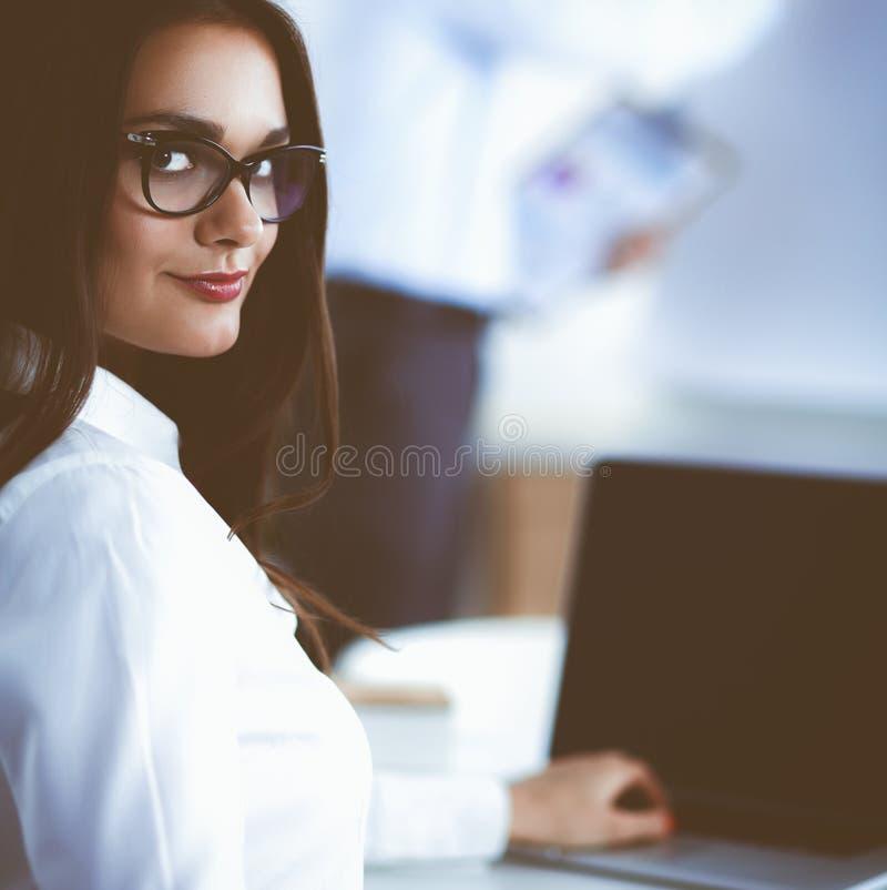 Привлекательная коммерсантка сидя на столе в офисе стоковое изображение