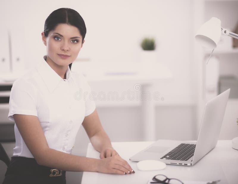 Привлекательная коммерсантка сидя на столе в офисе стоковая фотография