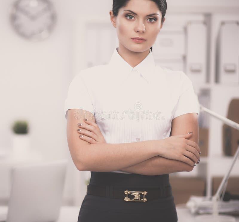 Привлекательная коммерсантка с ее оружиями пересекла положение в офисе стоковые фото