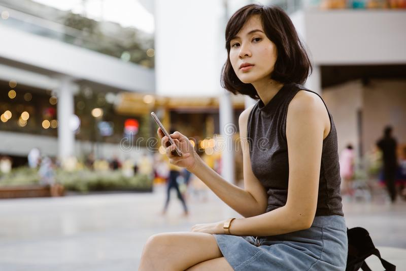 Привлекательная красивая азиатская женщина используя телефон mobil к sms стоковое изображение rf