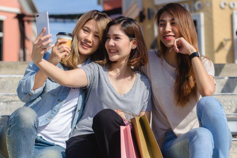 Привлекательная красивая азиатская женщина используя smartphone пока ходящ по магазинам в городе Счастливое молодое азиатское под стоковое изображение rf