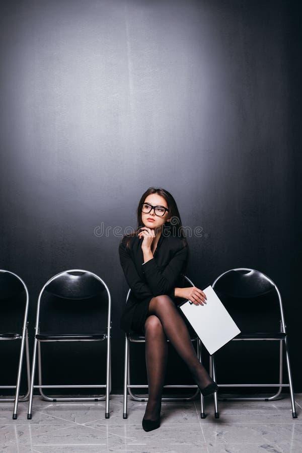 Привлекательная красивая студентка костюма держа файл встречи сидя на стуле и смотря работу пустой области думая планируя fe стоковое изображение rf