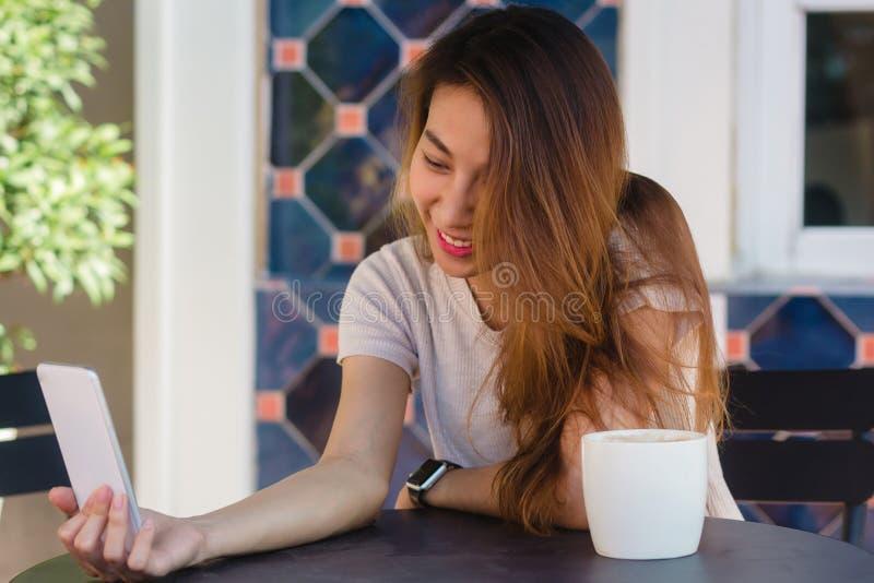 Привлекательная красивая счастливая молодая азиатская женщина принимая selfie используя умный телефон на кафе стоковое изображение rf