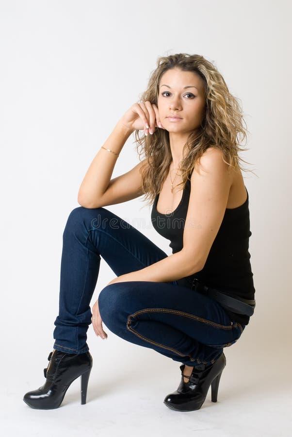 Привлекательная курчавая девушка в джинсах стоковые изображения