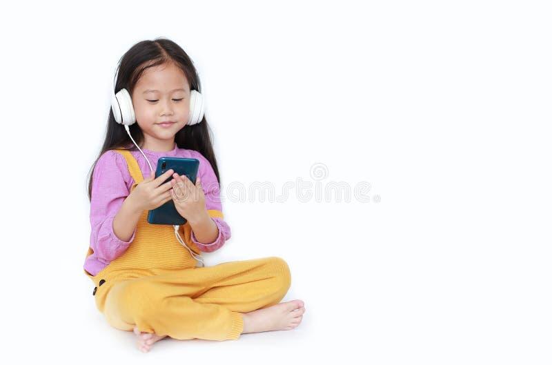 Привлекательная маленькая азиатская девушка ребенка в розов-желтых dungarees сидя с наушниками к наслаждается слушая музыкой смар стоковые изображения