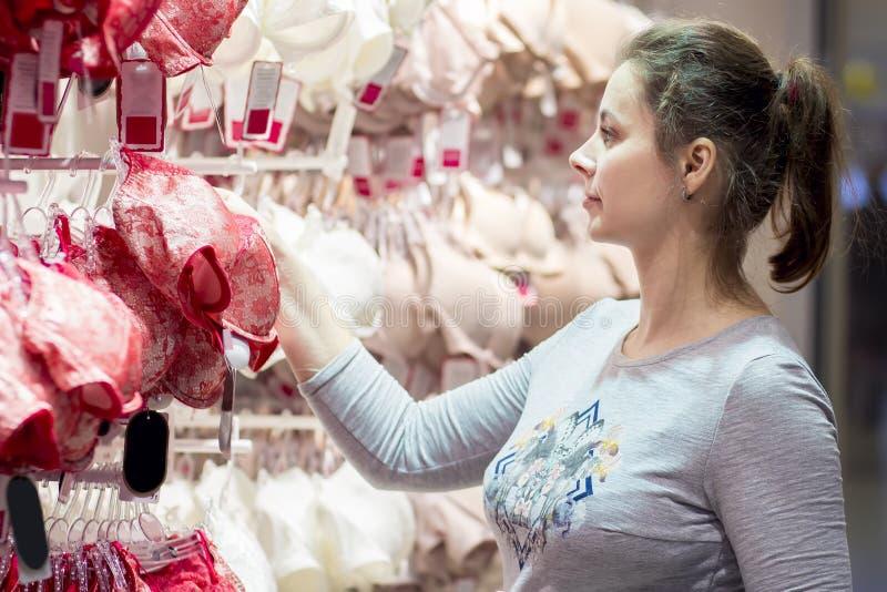 Привлекательная маленькая девочка в магазине нижнего белья выбирает бюстгальтер Довольно славная женщина в магазине модной одежды стоковые фотографии rf