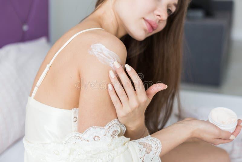 Привлекательная маленькая девочка в одеждах ночи прикладывает сливк для того чтобы снять кожу с и трет ее пока делающ процедуры п стоковое изображение
