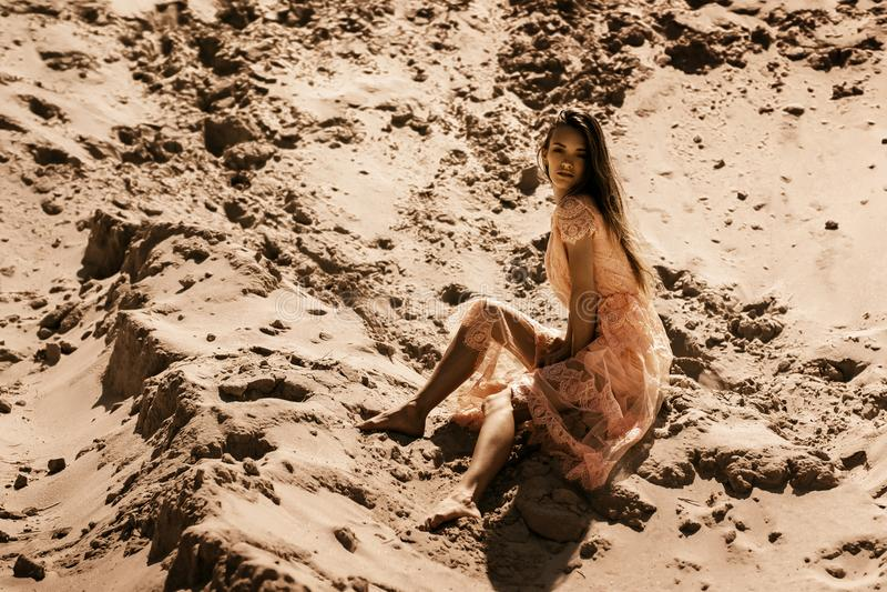 Привлекательная маленькая девочка в розовом платье сидит на песке стоковая фотография