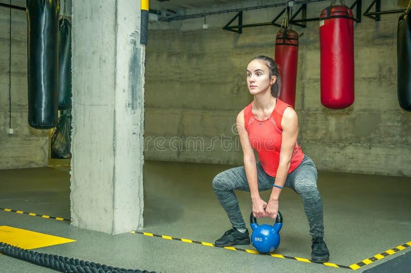 Привлекательная маленькая девочка сидит на корточках разминка в спортзале для мышц ног с тяжелым весом колокола чайника, трениров стоковые фото