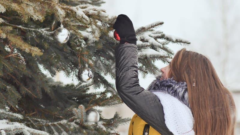 Привлекательная маленькая девочка с длинными волосами в костюме зимы представляя против снежного дерева Девушка шнурует шарики ро стоковое изображение rf