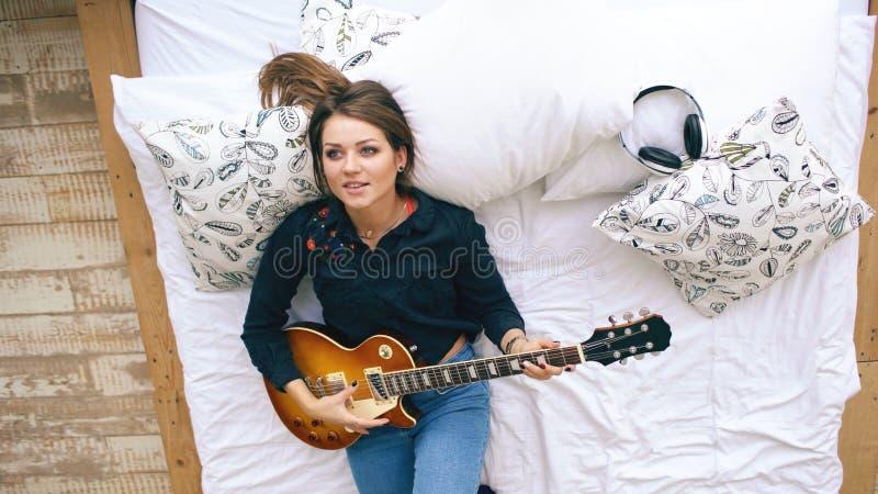 Привлекательная маленькая девочка уча сыграть ложь электрической гитары на кровати в спальне дома внутри помещения стоковое фото