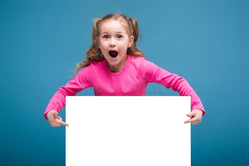 Привлекательная маленькая милая девушка в розовой рубашке с обезьяной и голубые брюки держат пустой плакат стоковые фото