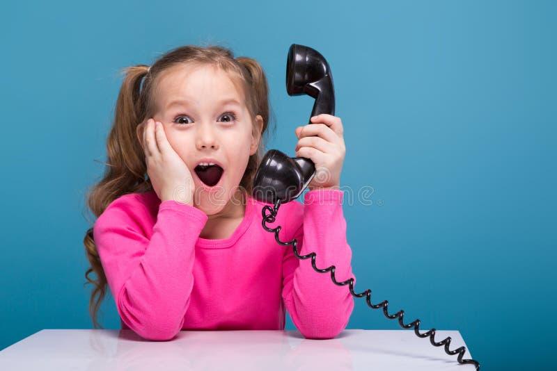 Привлекательная маленькая милая девушка в розовой рубашке с обезьяной и голубые брюки проводят пустой плакат и дискуссии телефон стоковые изображения rf