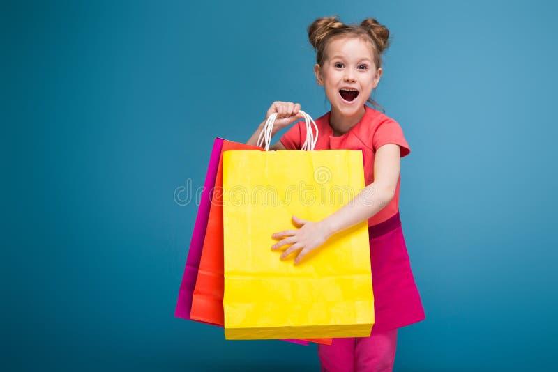 Привлекательная маленькая милая девушка в розовом платье держит фиолетовую бумажную сумку стоковые изображения