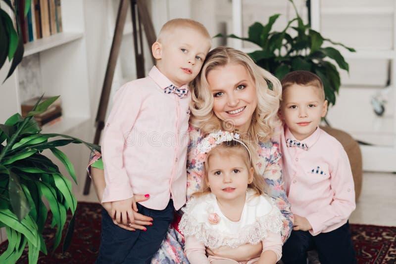 Привлекательная мать представляя с 3 милыми детьми дома стоковое изображение