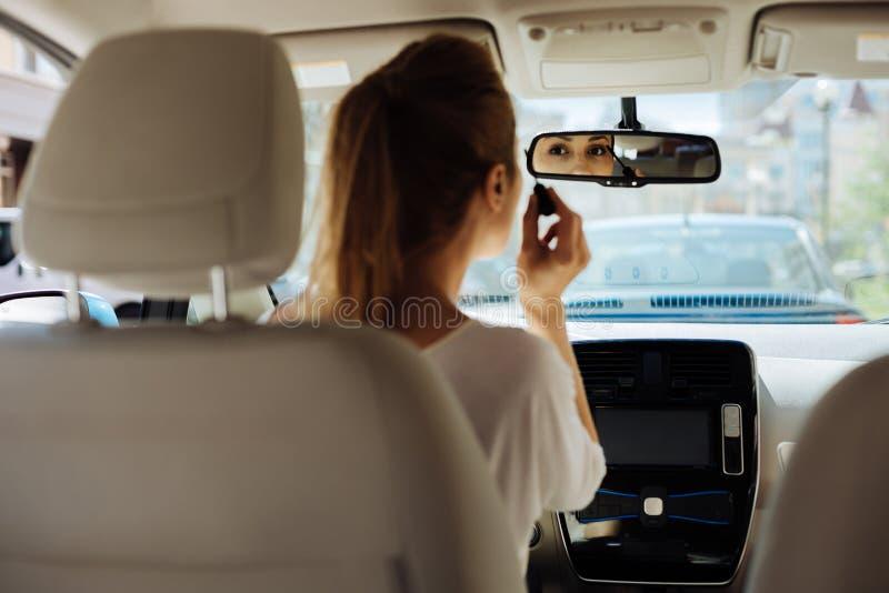 Привлекательная милая женщина смотря в зеркало заднего вида стоковая фотография rf