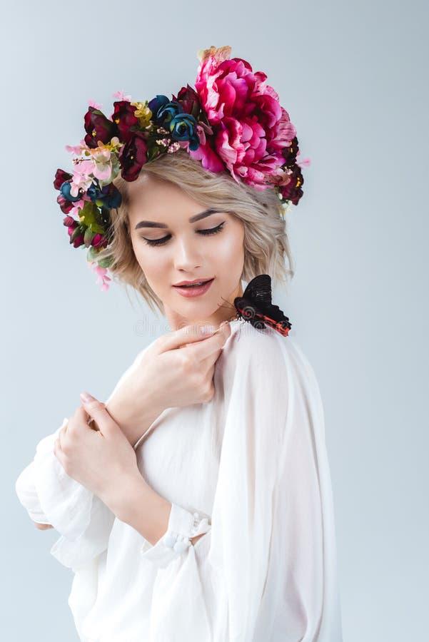 привлекательная модель представляя во флористическом венке с бабочкой на плече стоковые фото