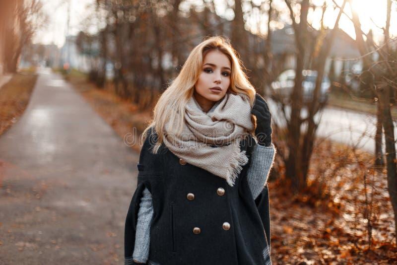 Привлекательная модная молодая женщина в стильном теплом outerwear осени стоящ и смотрящ камера стоковое фото rf
