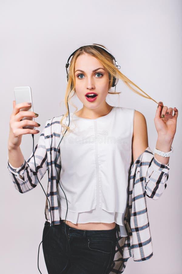 Привлекательная молодая белокурая женщина с большими белыми наушниками слушая музыку и читая сообщения на iPhone Милая девушка стоковое изображение rf