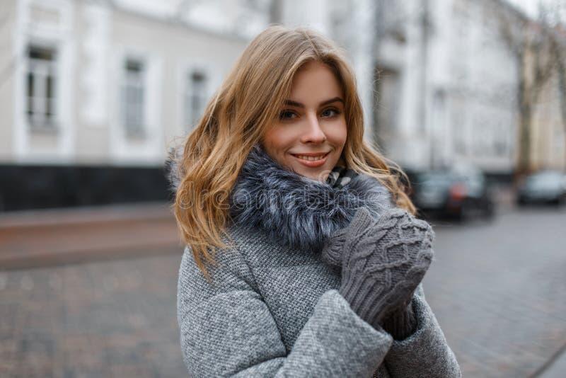Привлекательная молодая белокурая женщина с красивой улыбкой в стильном теплом outerwear зимы в связанных стойках mittens в город стоковые изображения rf