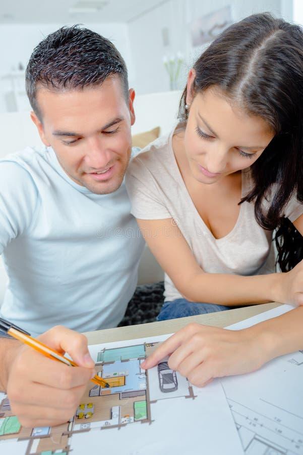Привлекательная молодая взрослая пара смотря дом планирует стоковое изображение rf